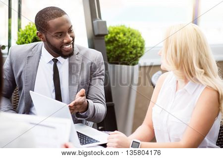 Involved in communication. Pleasant delighted colleagues talking and sitting at the table while working in the office