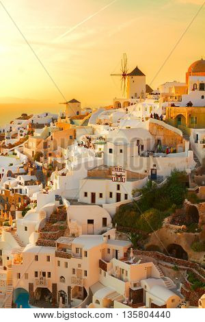 famouse pink and orange sunset of Oia with windmill, Santorini
