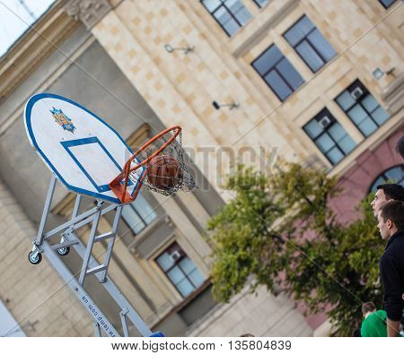 KHARKOV UKRAINE - JUNE 11 2016: Man throws ball into the ring streetball competitions on Freedom Square in Kharkov