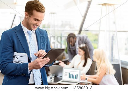 Share positivity. Cheerful smiling handsome man using tablet and holding newspaper while his colleagues working in the background