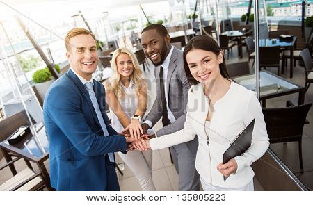 Ready to work. Pleasant cheerful colleagues holding hands together and expressing joy while smiling