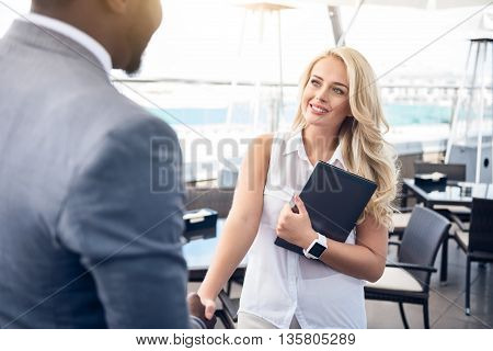 Pleasant cooperation. Cheerful glad beautiful woman shaking hands with her colleague while standing in the office