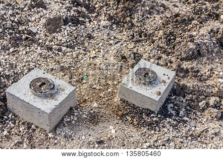 Round water metal hatch on square cement manhole are picking from the ground. Provide access for shutoff valves.