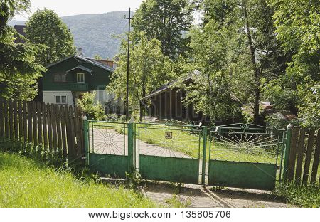 Sinaia, ROMANIA - June 18 2016: Green holiday house and fence in Sinaia mountain resort from Romania. SINAIA - June 18 2016