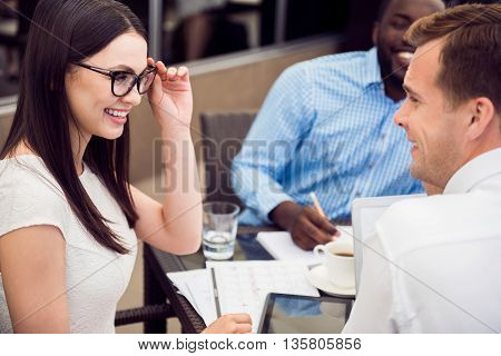 Pleasant talk. Nice beautiful smiling cheerful woman holding her glasses and talking with her colleague while sitting at the table