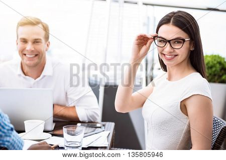 Express your emotions. Positive beautiful smiling woman touching her glasses and sitting at the table with her delighted colleagues