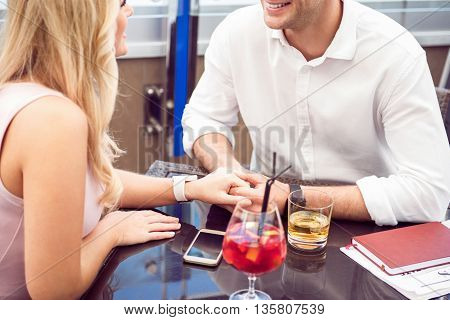 Love you deeply. Pleasant positive loving couple sitting at the table and resting together while holding hands