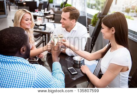 Celebrate your life. Pleasant cheerful delighted friends sitting at the table and drinking champagne while resting together