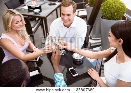 Happy celebration. Cheerful smiling friends drinking champagne and sitting at the table while expressing joy in the cafe