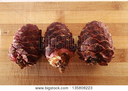 Three Cedar Cone On White Wood Background