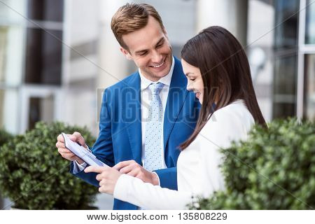 Think positively. Cheerful smiling professional colleagues holding folder and having a discussion while standing near office building