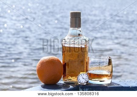Bottle of tequila and tumbler with watches on the shore of lake