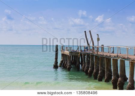 Wooden pier leading to the seacoast, natural landscape background