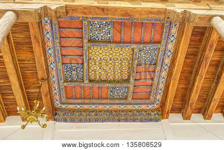 BUKHARA UZBEKISTAN - APRIL 29 2015: The colorful Islamic patterns on the carved wooden ceiling of Khakim Kushbegi Mosque of the Bahauddin Nakshbandi complex on April 29 in Bukhara.