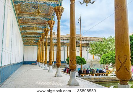 BUKHARA UZBEKISTAN - APRIL 29 2015: The shady gallery of Sheikh Naqshband Mausoleum decorated with the slender pillars and islamic ornaments on ceiling on April 29 in Bukhara.