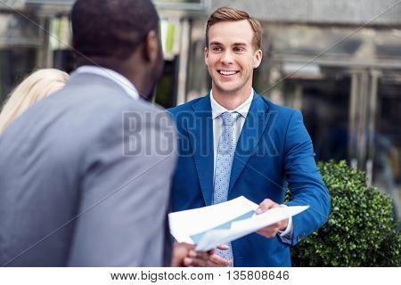 Here you are. Pleasant cheerful colleagues holding papers and standing near office building while expressing gladness