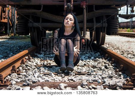 Young beautiful girl in black dress and nylons sitting on rail tracks and daydreaming, eyes closed, cargo wagons in background