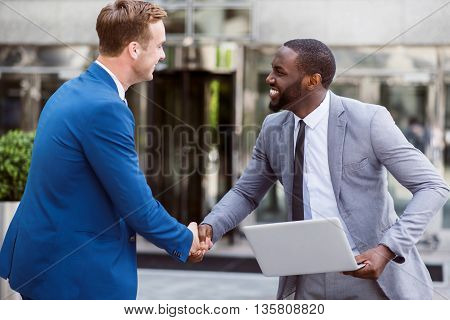 Glad to see you. Cheerful delighted smiling colleagues shaking hands while standing near office building and expressing joy