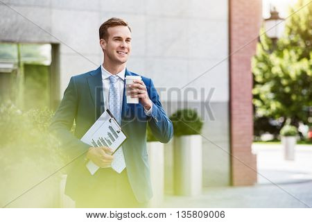 Positive look. Cheerful handsome confident man drinking coffee and holding folder while standing near office building