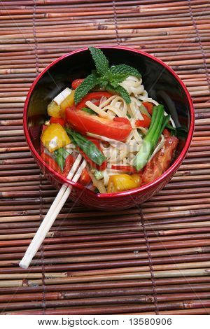 A colorful asian dish of noodles over a bamboo placemat