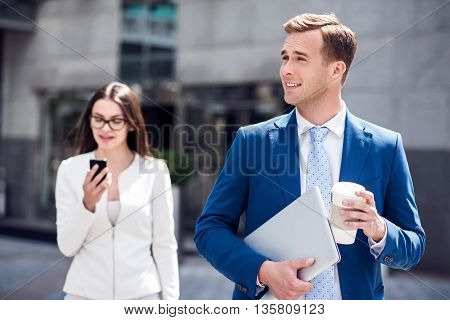Busy life. Pleasant handsome confident man holding laptop and drinking coffee while beautiful woman standing in the background