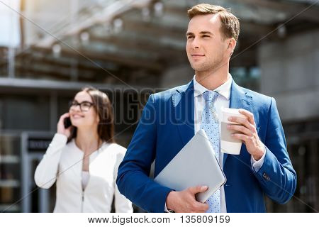 Feel the taste of life. Cheerful handsome confident man drinking coffee and standing near office building while beautiful talking on cell phone in the background