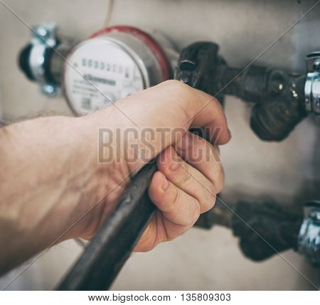 Male plumber fixing water meter with adjustable wrench.