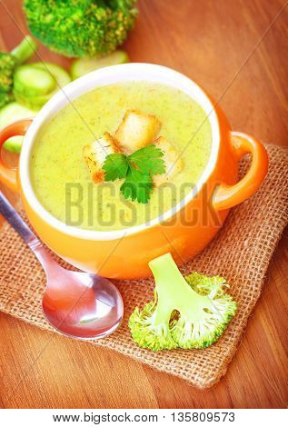 Closeup on little orange bowl with hot tasty cream soup prepared with broccoli, homemade healthy food, vegetarian meal concept