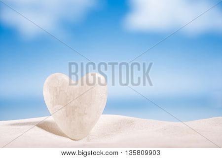 white crystal heart on white sand beach, ocean,  sky and seascape