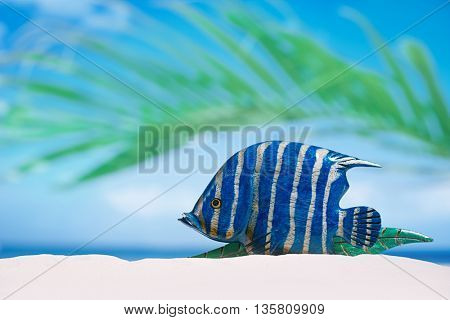 tropical fish on white sand beach sand under sun light, shallow dof