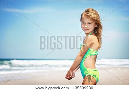 Portrait of a cute little girl on a beach, spending vacation in a summer camp on a seashore, happy healthy childhood