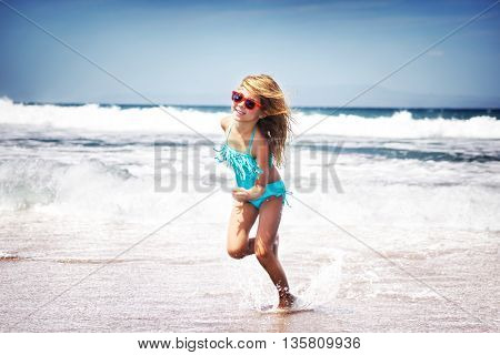 Happy little joyful girl playing on a beach, running having fun outdoors, with pleasure spending summer holidays near the sea, happy healthy childhood