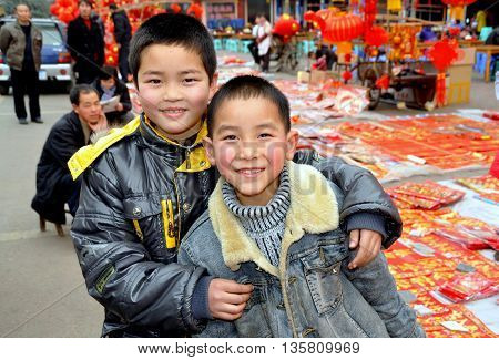 Pengzhou China - February 7 2010: Two Chinese boys are all smiles in Long Xing Square near displays of Chinese Lunar New Year decorations