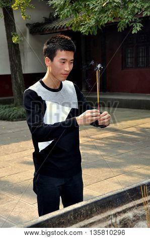 Chengdu China - November 8 2010: Young Chinese man holding burning incense sticks prays in a quiet courtyard at the 17th century Wenshu Buddhist temple
