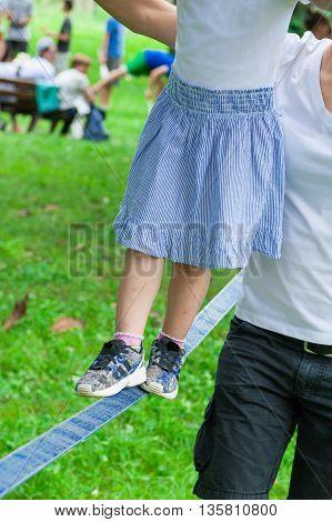 mother helps her child walking on the slackline