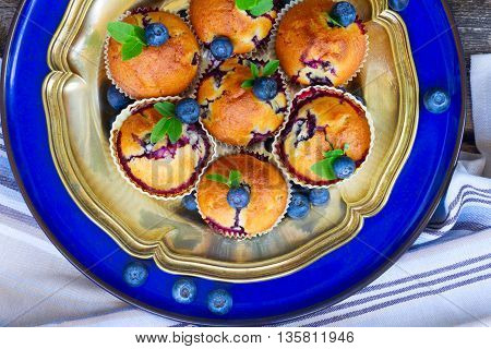 plate of baked cupcakes with blueberry on table