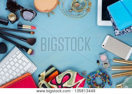 styled feminine desktop - woman fashion flat lay items on blue wooden background, copy space, top view