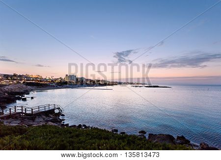 Photo of sea in protaras cyprus island with rocks and hotels at sunset.