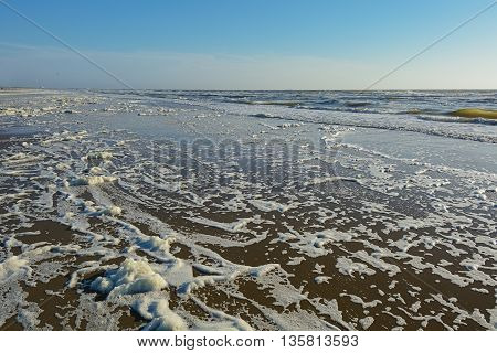 Beach with sea foam on the shore of the North Sea.