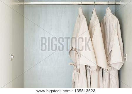 Bathrobe Hanging On Rail In Wooden Wardrobe