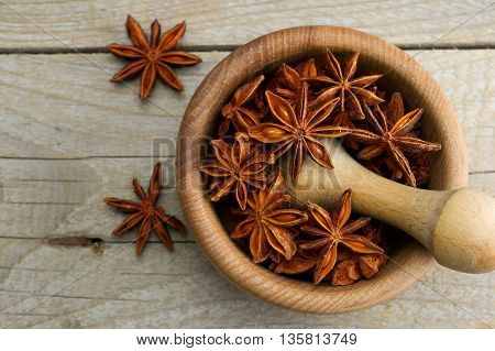 star anise in a wooden mortar on a wooden background