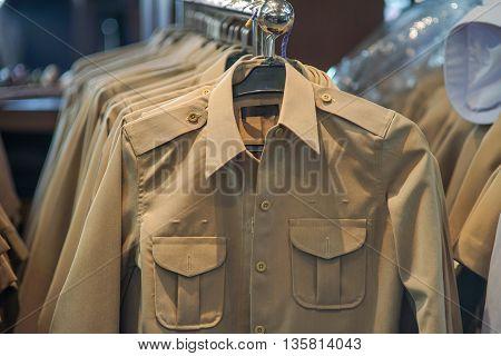 Khaki uniform shirt on a clothes rack