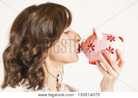 Close up portrait of happy young beautiful woman kissing pink piggy bank, studio shot on white background