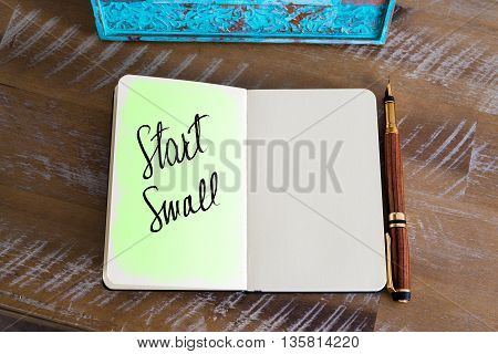 Handwritten Text Start Small over notebook, copy space available