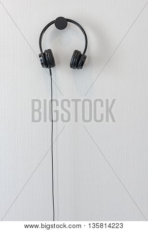 modern black head phone hanging on white wall
