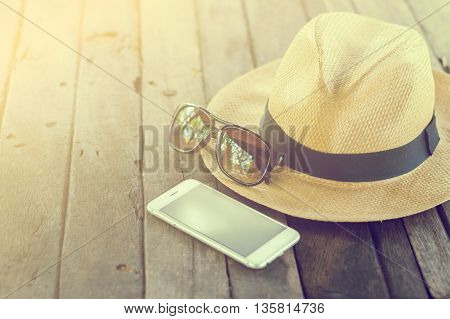 Set of vacation accessory such as mobile phone,glasses,hat  on wooden vintage background,vacation concept