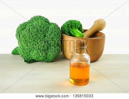 Fresh Broccoli in wooden mortar and seed oil in vintage bottle