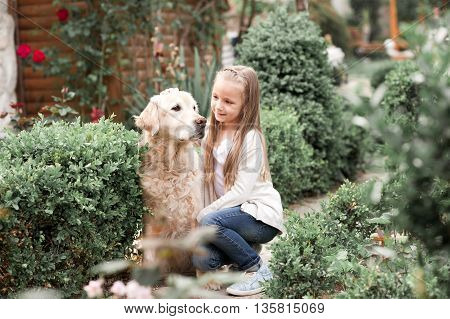 Cute baby girl 3-4 year old holding labrador pet outdoors. Togetherness. Friendship.