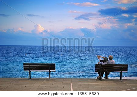 Camogli, Ligure, Italy - 14 June 2015: older couple on a bench by the sea in feelings of love.  On the waterfront of the Mediterranean Sea in Camogli, photo captured in an urban environment Camogli, Ligure, Italy.