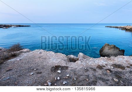 Photo of sea in protaras cyprus island with rocks and boats at sunset.